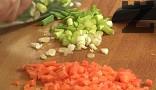 В сгорещеното олио задушаваме нарязания на кубчета морков. Наситняваме лука, прибавяме и него в тенджерата под налягане.