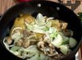 Пържим до златисто. Запържваме нарязания бекон, кромид лук, праз и гъби. В тавичка слагаме пилешките бутчета и запържените зеленчуци.