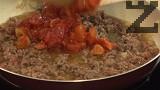 Поставяме стерилизираните домати, поръсваме със сол, наситнен риган и кимион.