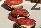 В чиния за сервиране подреждаме продуктите в следната последователност – филийка изпечен патладжан, колелце домат, сирене. По този начин редим 3 пласта, декорираме с пресен риган.
