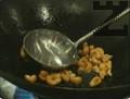 В тиган уок се сгорещява 1 с.л. олио и се запържва кашу, докато ядките придобият златист цвят. Изваждат се от съда и се оставят настрана.