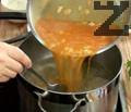 Наливаме малко от бульона, разбъркваме и изсипваме запръжката в тенджерата с месото. Добавяме нарязаните на едро картофи и консервираните домати.
