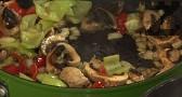 Добавяме едро нарязаните печурки, увеличаваме силата на огъня. След кратко пържене, добавяме нарязаните на едри парчета чушки.