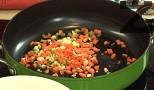 Режем останалите 2 стръка пресен лук /½ глава кромид лук/ и скилидките чесън на ситно, а морковите - на кубчета. Задушаваме зеленчуците в загрята мазнина за 20-30 сек.