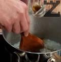 Изсипваме ориза в тенджера със студена вода и сваряваме. Наливаме прясно мляко и орехов ликьор, добавяме захар.