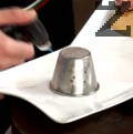 Нагряваме с горелка тимбалчетата и обръщаме панакотата в чиния за сервиране. Декорираме десерта с топинг по избор.