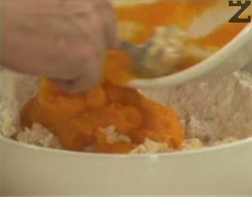 Към брашното добавяме тиквата, разбъркваме добре. Замесваме меко тесто, прехвърляме и едро смлените орехови ядки, както и стафидите.