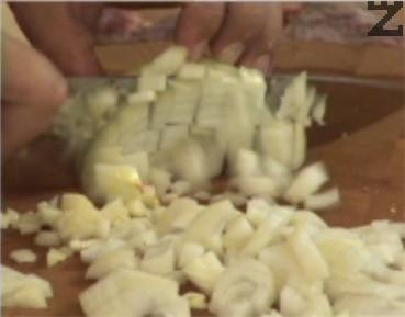 Нарязваме лука на ситно, поставяме го в тенджера под налягане, заедно със скилидките чесън.