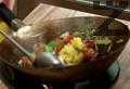 Загряваме олио в уок и запържваме джинджифил и чесън. Прибавяме нарязаните на кубчета чушки, праз и шайбите ананас. Поръсваме с натриев глутамат, добавяме кетчуп.