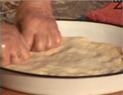 Мажем тава с диаметър 40 см със свинска мас, слагаме втасалото тесто, разстиламе с ръце и отново намазваме със свинска мас.