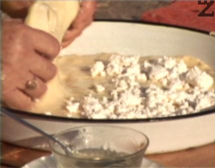 Поръсваме до половината с натрошено сирене, прегъваме тестото на две и отново разточваме с ръце, за да покрием дъното на тавата.