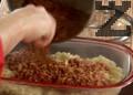 В намаслена тава нареждаме пластове от задушено зеле и кайма. Отделяме дафиновия лист и печем около 45 мин.