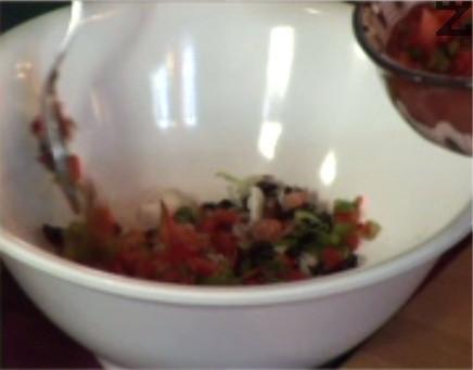 Прехвърляме маслините и нарязаните чушки. Поръсваме с 1 щипка сол, наливаме балсамовия оцет, разбъркваме.