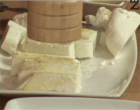 Нарязваме сиренето на парченца, които овкусяваме с босилек, черен пипер и зехтин. Оставяме ги за кратко в хладилник, за да поемат ароматите.