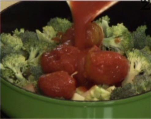 След 2-3 мин. добавяме наситнения чесън и стерилизираните домати. Задушаваме под капак за 1-2 мин., поръсваме с риган и магданоз.