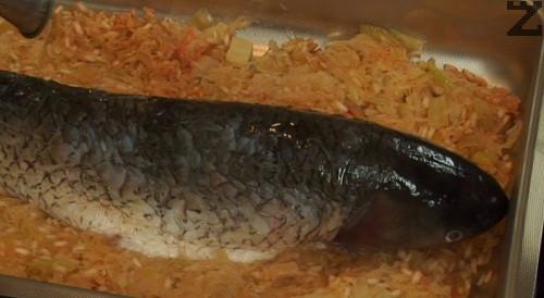 Отгоре слагаме рибата, поливаме със струйка мазнина, поръсваме с червен пипер. Наливаме 1 ч.ч. вода, поставяме в средата на умерено затоплена фурна. Печем на 180 градуса за 40 мин.