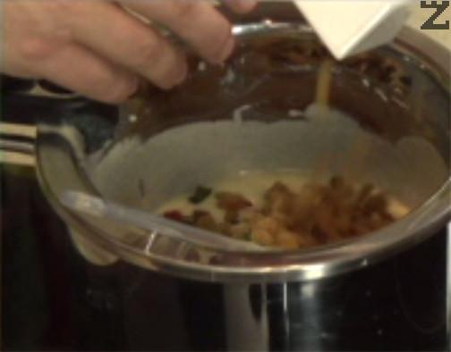 Прибавяме захаросаните плодове, стафидите и ситно нарязаните орехови ядки. Разбъркваме добре, оставяме сместа в хладилник за около 2 часа.