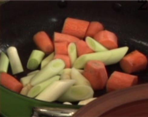 Нарязваме на едро морковите и праза, а целината – на кубчета. Прехвърляме зеленчуците в тигана, заливаме с червеното вино.