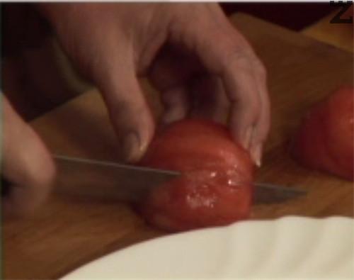Обелваме краставицата и я нарязваме на полумесеци. Белим доматите, режем и тях.