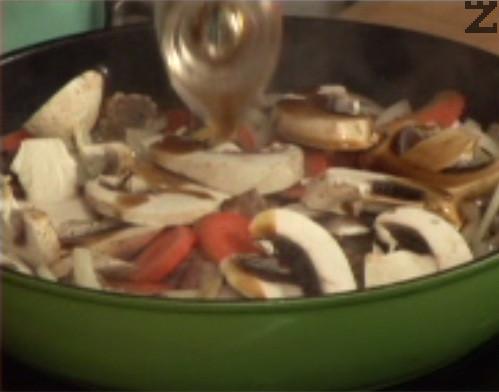 След като месото се позачерви, прехвърляме и зеленчуците. Наливаме соев сос, продължаваме да задушаваме.