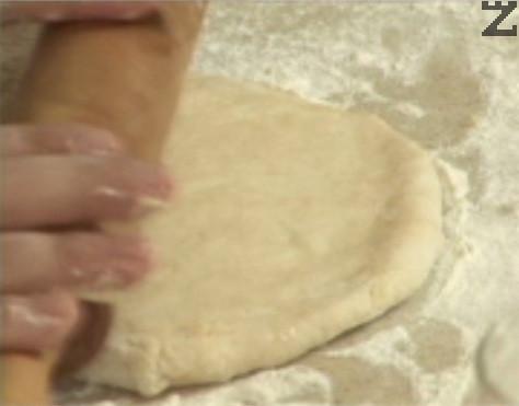 Разделяме тестото на 2 равни части, всяка от които разточваме на тънка кора с елипсовидна форма, като обилно поръсваме с брашно.