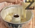 В голяма купа слагаме останалото тесто, добавяме кокосови стърготини и разбъркваме. Изсипваме част от кокосовото тесто в намаслена и набрашнена форма за кекс.