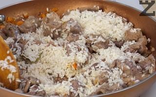 Накиснатия по този начин ориз се слага в тигана при месото, разбърква се и се слага в тава за печене.