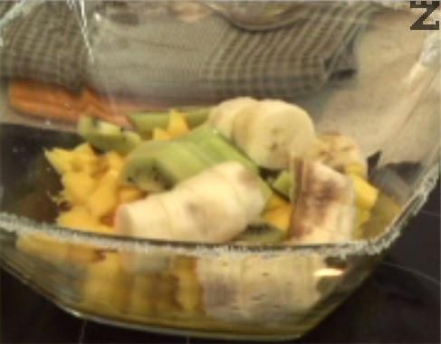Нарязваме мангото на кубчета и ги прехвърляме към дресинга. Измиваме и обелваме кивито, режем го на половинки. Добавяме и колелцата банан.