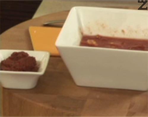 Слагаме обелените и нарязани на дребно стерилизирани домати, прибавяме и разтвореното в малко вода доматено пюре.