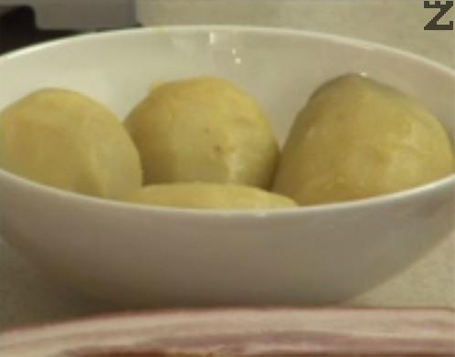 Предварително сваряваме целите небелени картофи. Нарязваме бекона по дължина на филийки с дебелина около 3 мм.