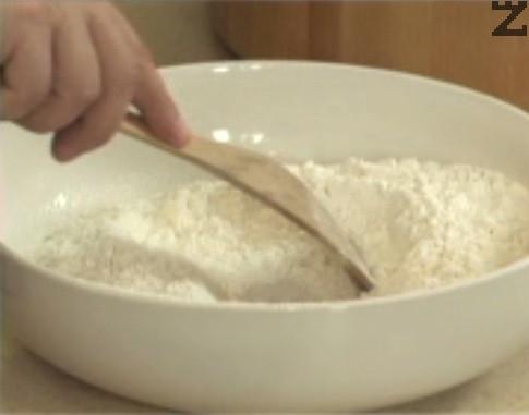 Пресяваме брашното, в центъра оформяме кладенче. Вътре слагаме яйцето, посоляваме и наливаме зехтин.