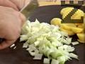 Нарязваме картофите на резени, a праз лука - на едро. Загряваме олио и запържваме праза.