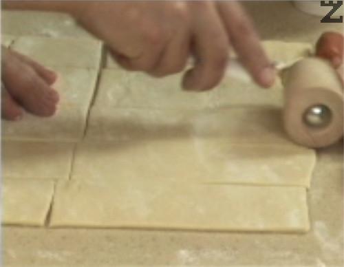 Нарязваме ледено студеното тесто на 10 лентички. С помощта на валяк леко изтъняваме тестото и го надупчваме по краищата с вилица.