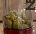 Пюрираме маслини със сол и зехтин. Добавяме сух хляб и кафява захар и продължаваме да пюрираме. Нарязваме червен салатен лук на тънки ивици.