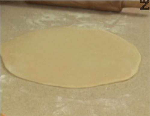 След като извадим тестото, го оставяме за 10 мин. на стайна температура. Разделяме го на 2 части, които разточваме на тънки кори върху обилно набрашнена повърхност.