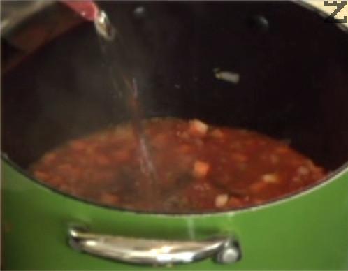 Прибавяме наситнения чесън и обелените и нарязани на дребно стерилизирани домати. Слагаме и доматеното пюре, наливаме 1,2 л гореща вода.