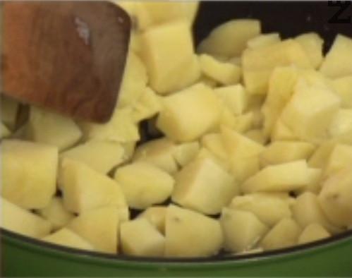 В тиган наливаме олио и след като загрее, слагаме охладените картофи. Пържим ги, като в първите 2 мин. не разбъркваме.