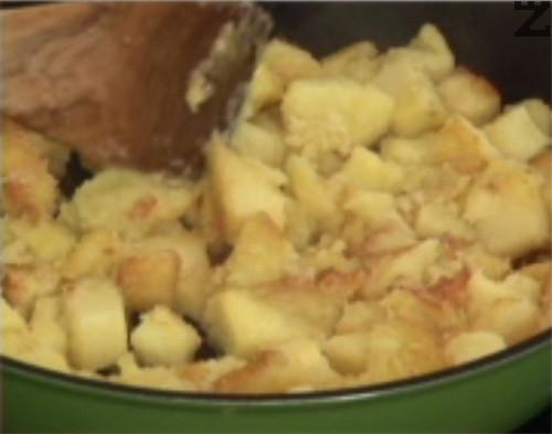 Нарязваме чесъна на по-едро и го прехвърляме към картофите. Изчакваме за около 8-10 мин., докато продуктите се запържат равномерно, като не бъркаме често.