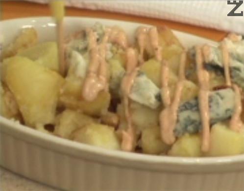 Прехвърляме картофите в съд за сервиране, отгоре слагаме едро натрошеното синьо сирене. Поливаме със соса, поръсваме с босилек.