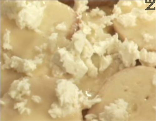 Отгоре натрошаваме половината сирене и поливаме с 1/3 от разтопеното масло. По същия начин оформяме още един ред на тутманика. Накрая покриваме с филийки, напоени в яйчената смес и поливаме с останалото разтопено масло.