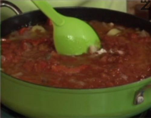 Добавяме настърганите домати, наливаме 2 ч.ч. гореща вода. Леко разбъркваме и поръсваме с подправките, слагаме счукания чесън. Разбъркваме, оставяме соса да къкри на бавен огън, докато част от течността се изпари. Варим в продължение на 30 мин. или докато соса се уплътни.