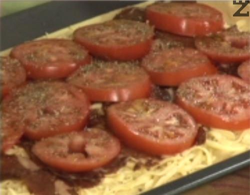 Слагаме нарязаните на филийки домати, поръсваме с риган. Поливаме с няколко капки зехтин, леко прегъваме краищата на тестото.