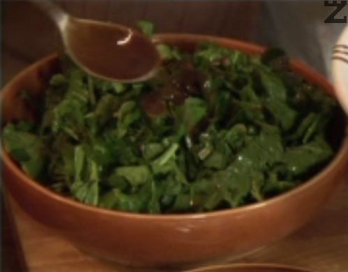 В купа поставяме зелената салата и руколата. Поливаме с част от дресинга и леко разбъркваме с ръце. Добавяме настърганото сирене, счуканите орехи, нарязаните на ситно маслини, крутоните и целите сушени домати.