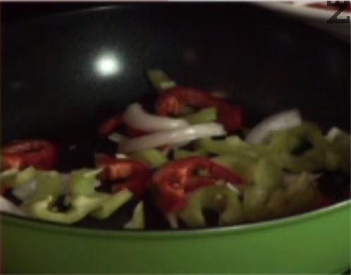 Нарязваме лука и чушките на ивици и ги запържваме за кратко в сгорещен зехтин. След като зеленчуците леко омекнат, добавяме нарязаната на кубчета създърма. Запържваме за кратко.