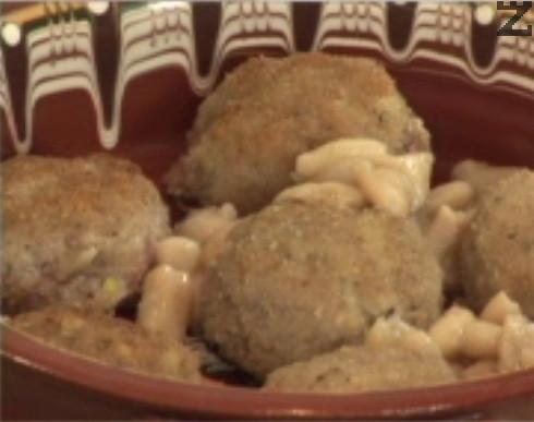 Подреждаме кюфтенцата на дъното на глинен съд, между тях слагаме сварен фасул и поливаме със соса.