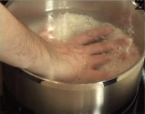 Изплакваме ориза няколко пъти в студена вода. След като отмием нишестето и течността стане бистра, го прехвърляме в тенджера. Наливаме толкова студена вода, че като си сложим ръката върху ориза, да се показва само кокалчето на средния ни пръст. Когато водата заври, намаляваме котлона на най-ниска ст