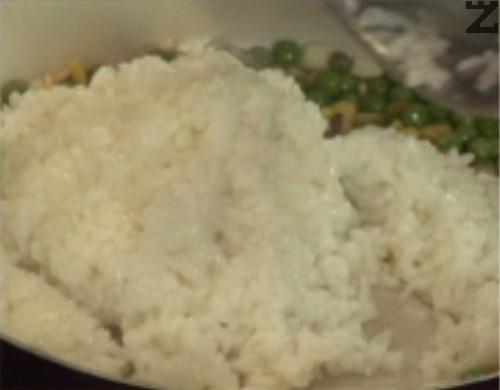 Прехвърляме и ориза, поръсваме със сол и захар. Притискаме леко ориза, след което запържваме продуктите, като периодично разбъркваме.