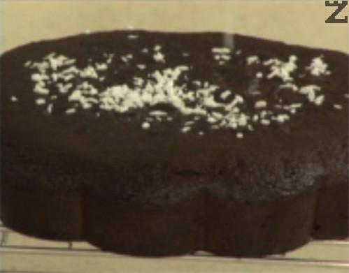 Едва тогава вадим кекса от формата, обръщаме го върху решетка и го оставяме да се охлади напълно. Накрая поръсваме обилно повърхността на кекса с кокосови стърготини.