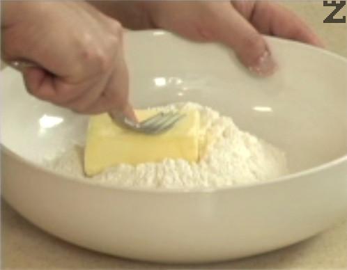 В купа поставяме предварително пресято брашно. Добавяме 3 с.л. пудра захар и краве масло, претриваме за кратко с вилица. Прибавяме жълтък и ванилова захар и бъркаме, докато се получат хлебни трохи.