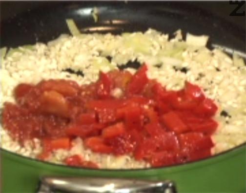Добавяме ориз, пържим за секунди и слагаме нарязани печени чушки и наситнени домати. Разбъркваме, посоляваме и наливаме 450 мл гореща вода.